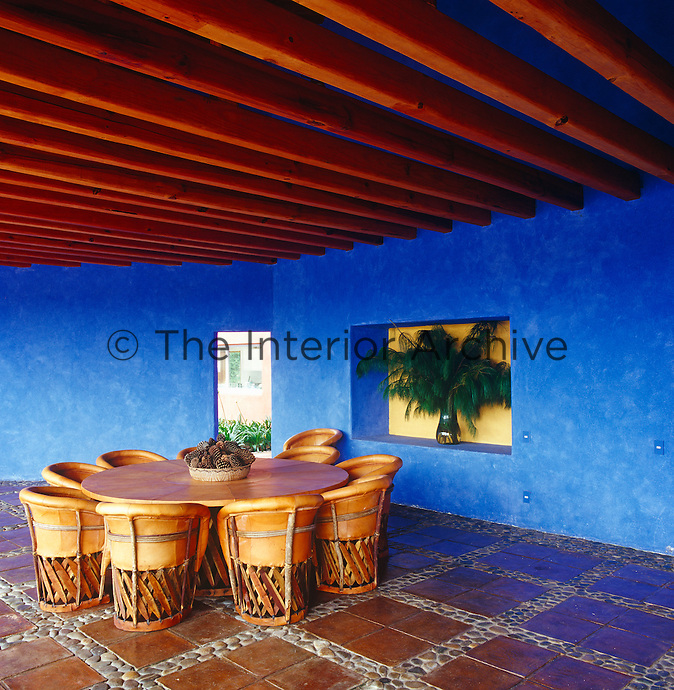The loggia has distinctive blue walls and a floor made of a combination of terracotta tiles and pebbles