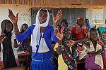 Basamat Alnoor Jakolo Aldabi sings with students in her school classroom in the Kaya Refugee Camp in Maban County, South Sudan. The camp shelters thousands of refugees, including this teacher, from the Blue Nile region of Sudan, and Jesuit Refugee Service, with support from Misean Cara, provides educational and psycho-social services to both refugees and the host community.