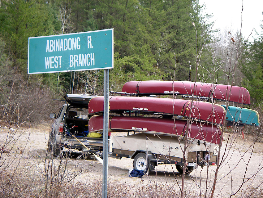 Vehicle pulling trailer of canoes parked near a sign for the Abinadong River in Ontario Canada
