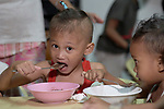 A boy enjoys a meal in the United Methodist Church in the Parola neighborhood of Tondo, a poor section of Maniila, Philippines. Nursing students from the Mary Johnston College of Nursing regularly visit the neighborhood to do health education and monitor the health of residents, at the same time running  a feeding program for neighborhood children.<br /> <br /> The nursing school is supported by United Methodist Women.