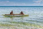 Locals boarding a traditional canoe in Funafuti, Tuvalu