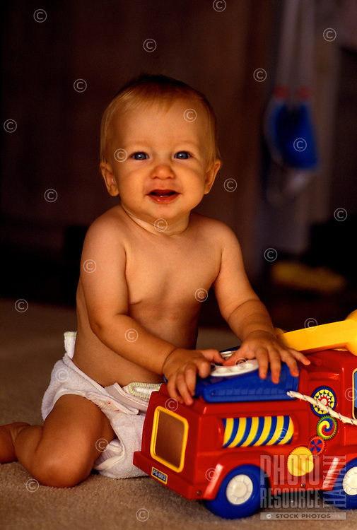 A cute baby boy wearing a diaper kneels on the floor while playing with a soft vinyl truck.