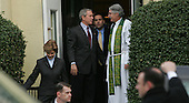United States President George W. Bush talks to Reverend Dr. Luis Leon, the rector of St. John's Episcopal Church after attending  the eight AM service at the church in Washington, DC on January 16, 2005. On left: First lady Laura Bush . Secret Service agents are in the foreground. <br /> Credit: Dennis Brack / Pool via CNP