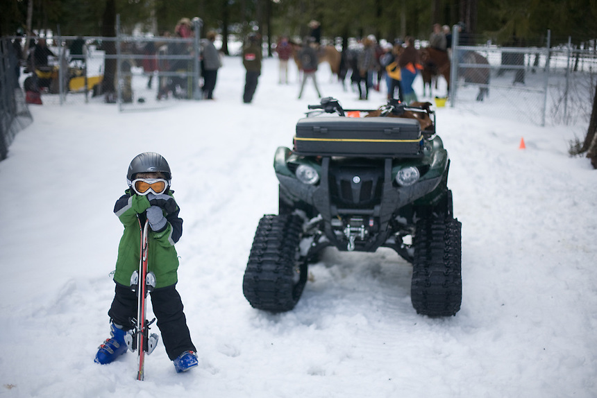 Avery Smart, 4, stands inside the opening gates for horseback riders, and in this case skiers, at the Bonner County Fairgrounds in Sandpoint, ID. His father, Matt Smart, organized the first ever Skijoring Event during the Sandpoint's annual Winter Carnival.