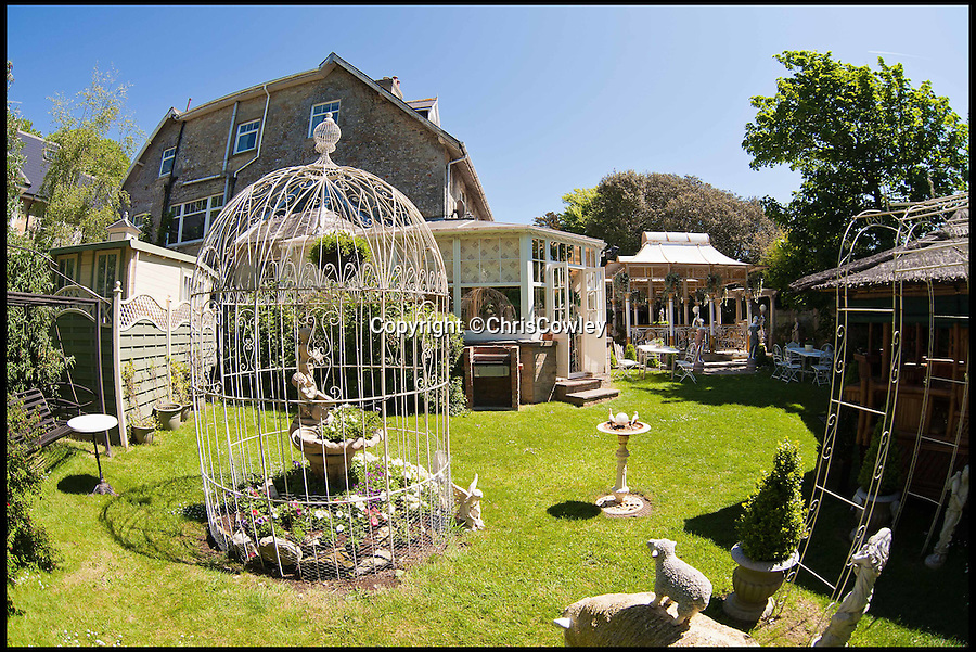 BNPS.co.uk (01202 558833)<br /> Pic: ChrisCowley/EnchantedManor/BNPS<br /> <br /> **Please use full byline**<br /> <br /> The garden.<br /> <br /> Sleeping Beauties and Cinderallas take note - make a wish and this luxury fairytale hotel could be yours for a cool £1.5 million.<br /> <br /> With 11 sumptuous suites - all of which are decked out in fairtytale style with four-poster beds - the Enchanted Manor is the stuff dreams are made of.<br /> <br /> Coupled with idyllic sea views, the unique 5* property near Niton on the Isle of Wight has become a bolthole for couples seeking fairytale romance.<br /> <br /> Once a historic Victorian manor house, owners Ric and Maggie Hilton set about creating their dream come true after saving the grand building from ruin in 2006.<br /> <br /> The property is being on the market for £1.5 million with property guru Sarah Beeny's online estate agents Tepilo.