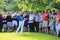 Rory McIlroy (NIR) plays his 2nd shot from the trees after a wayward drive on the 18th hole during Friday's Round 2 of the 2014 Irish Open held at Fota Island Resort, Cork, Ireland. 20th June 2014.<br /> Picture: Eoin Clarke www.golffile.ie