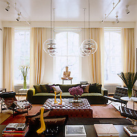 "In the living area the oversized tufted ottoman by De Padova is flanked on one side by a pair of Mies van der Rohe ""Barcelona"" chairs and on the other by a green low-slung velvet Minotti sofa"
