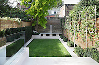 Steps lead down from the patio to the lawn which is edged with paved paths and neatly spaced flowerbeds