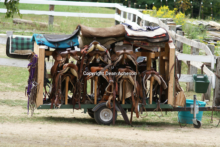 Saddles at a riding stable wait their mounts and riders.