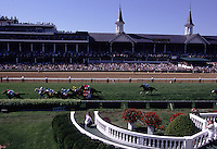 Horses run down a turf track at Churchill Downs.