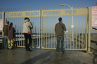 A group of people watch large surf through the locked gate of the Ocean Beach Pier on Wednesday, December 5 2007.  A large storm swell hit San Diego shores forcing the temporary closure of the pier.