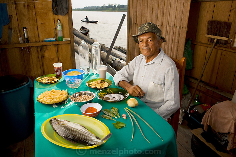 João Agustinho Cardoso, a fisherman, in his floating house on a branch of the Solimoes River with his typical day's worth of food in  Manacapuru, Brazil. (From the book What I Eat: Around the World in 80 Diets.) The caloric value of his day's worth of food for a typical day in the month of November was 5200 kcals. He is 69 years of age; 5 feet 2.5 inches tall and 140 pounds.  João's new house has no electricity and the toilet is simply the end of the big balsa wood logs the house is floating on. There is, however, running water, and plenty of it, in the half-mile-wide branch of the river they live on. Unfortunately the water is not potable, but it is teeming with fish, including piranha, which can make swimming during the early morning or evening worrisome. The curimata in the photo is just one of dozens of species that makes its way onto João's table. Absent from his daily diet are any alcoholic or caffeinated beverages, eschewed by his Seventh-day Adventist religion.  MODEL RELEASED.