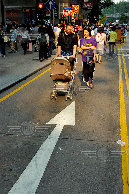 Couple in Causeway Bay with their baby in a pram.
