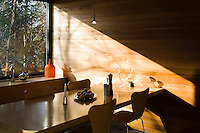 The cedar wood wall panelling in the dining area is bathed in soft evening light