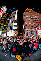 "Tourists appear on the Revlon ""Love is On"" big screen in Times Square, New York, New York USA."
