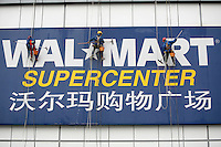 Cleaners scale down a Walmart sign while cleaning the exterior of a shopping center in Nanning, Guangxi Province, China..