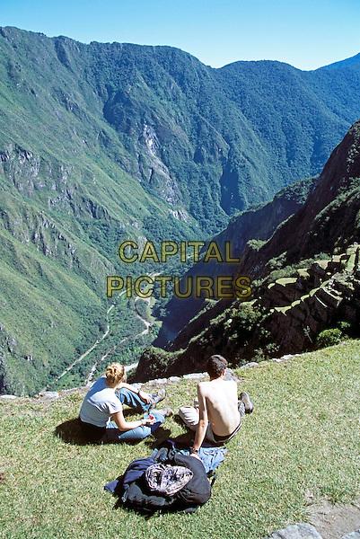 Machu Picchu, visitors sitting on terrace, Peru