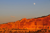 A moonrise with sunset highlighting a sandstone wall of Shafer Canyon in Canyonlands National Park, Utah.