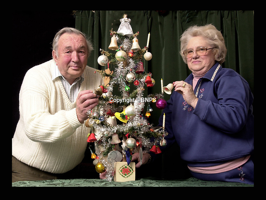 BNPS.co.uk (01202 558833)<br /> Pic: MikeSimmonds/BNPS<br /> <br /> Derek and Sybil Parker pictured in 2002.<br /> <br /> When it comes to a Christmas tree prudent Derek Parker is the ultimate scrooge - as he's had the same one for 80 years.<br /> <br /> Derek, 80, can't remember a time before the 3ft fragile tree and he's never known Christmas without it.<br /> <br /> His mother Lilly bought it in 1937 when he was three-months-old and after he married wife Sybil 60-years-ago he took it with him.<br /> <br /> The couple, from Crewkerne, bring it out every Christmas for their children, grandchildren and great-grandchildren to enjoy.