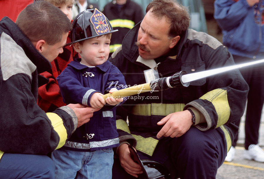 Two fire fighters helping young child with hose to put out fire demonstration in the midwest