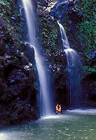 A honeymoon couple embrace under a waterfall on the road to Hana, Maui.