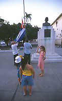 06 FEB 2003 - SANCTI SPIRITUS, CUBA - Children salute the Cuban flag as it is lowered at the end of the day after being flown at half mast in memory of the Colombia crew who died in the space shuttle disaster (PHOTO (C) NIGEL FARROW)