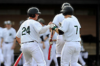 Left fielder Stephen Dowling (7) of the University of South Carolina Upstate Spartans, right, is congratulated by Zach Krider (24) after scoring a run in a game against the Winthrop University Eagles on Wednesday, March 4, 2015, at Cleveland S. Harley Park in Spartanburg, South Carolina. Upstate won, 12-3. (Tom Priddy/Four Seam Images)