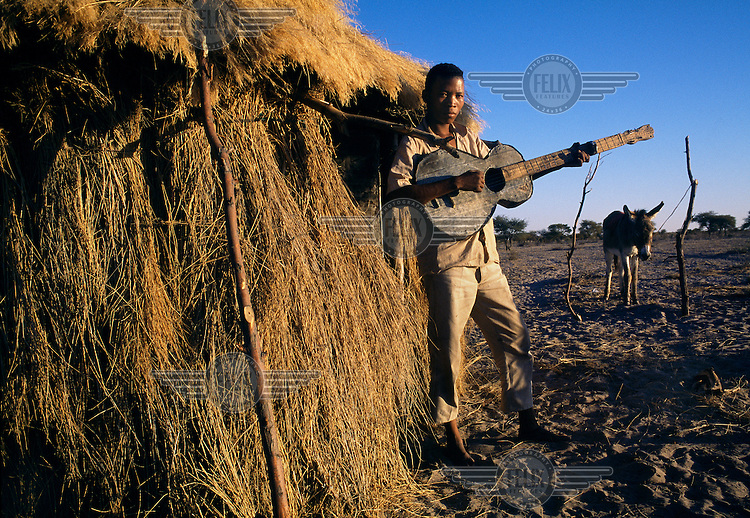 A youth with a guitar in the Xade settlement before the entire San population were removed, between 1997 and 2002, to a new location outside the Central Kalahari Game Reserve.