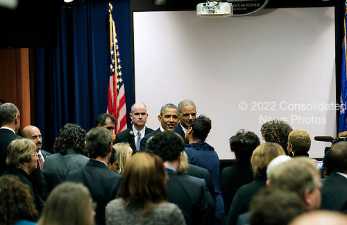 United States President Barack Obama and U.S. Attorney General Eric Holder visit staff members from the U.S. Department of Justice after delivering remarks on signals intelligence programs and how they can be used to protect national security while supporting foreign policy and respecting privacy and civil liberties, at the Department of Justice in Washington DC, on January 17, 2014.<br /> Credit: Aude Guerrucci / Pool via CNP