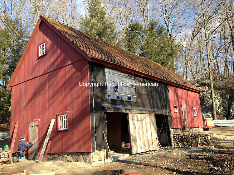 WOODBURY, CT - 22 Jan 2015 - 012215RH01 - A worker attaches a new door to a barn beside Woodbury resident Robert Cristiano's Orenaug Avenue home, which was built around 1721 by the Rev. Zachariah Walker. The workers of East Coast Barn Builders began taking down the structure on Oct. 10, tagging and sorting each beam, discarding those too deteriorated to reuse. Company owner Ed Cady Sr. said the restoration should be finished in about a week. Rick Harrison Republican-American