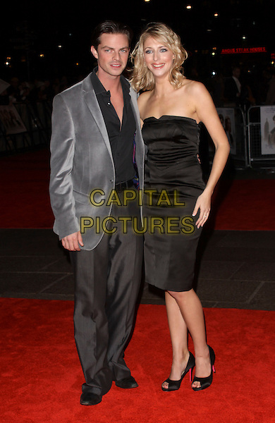"BRIAN FORTUNA & ALI BASTIAN.At the ""Me & Orson Welles"" UK Film Premiere, Vue West End, Leicester Sqaure, London, England, .18th November 2009..full length strapless black dress grey gray jacket trousers peep toe shoes shirt .CAP/AH.©Adam Houghton/Capital Pictures."