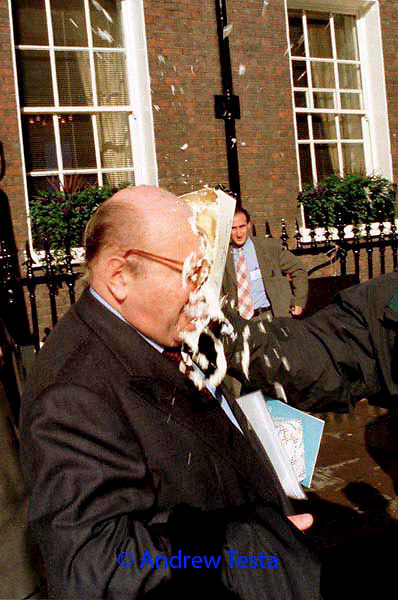 "Renato Ruggiero, Director General of the World Trade Organisation, getting a custard pie thrown in his face after giving a speech at a Trade, Investment and Environment conference in London. Protesters from the Biotic Baking Brigade who in recent weeks have pied  neoliberal economist Milton Friedman and Bob Shapiro, CEO of Monsanto, said "" to thoose who wish to dominate the world, the world replies, let them eat humble pie!"" 30/10/98.<br /> ©Andrew Testa"