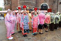 Nederland  Amsterdam  2016.  Boeddhadag op de Nieuwmarkt in Amsterdam. Viering van de geboorte van Boeddha. Tijdens de ceremonie begint het te regenen en worden er poncho's aangetrokken.. Foto Berlinda van Dam / Hollandse Hoogte