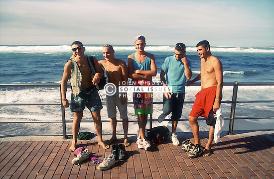 Group of young men standing together on seafront at Las Canteras beach; Las Palmas; Gran Canaria; Canary Islands,