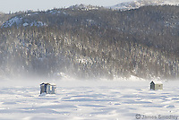 Ice fishing huts on a windy frozen lake in winter