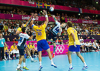 31 JUL 2012 - LONDON, GBR - Ciaran Williams (GBR) of Great Britain (second from right, in white, blue and red) shoots during the men's London 2012 Olympic Games Preliminary round match against Sweden at The Copper Box in the Olympic Park, in Stratford, London, Great Britain (PHOTO (C) 2012 NIGEL FARROW)