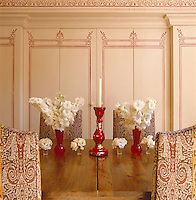 The cupboards behind the dining table and chairs in the kitchen are stencilled with a design inspired by a room in the Ashmolean Museum in Oxford