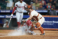 Robert Moore (1) of the Arkansas Razorbacks slides into home plate ahead of the tag by Texas Longhorns catcher Silas Ardoin (4) in game six of the 2020 Shriners Hospitals for Children College Classic at Minute Maid Park on February 29, 2020 in Houston, Texas. The Longhorns defeated the Razorbacks 8-7. (Brian Westerholt/Four Seam Images)