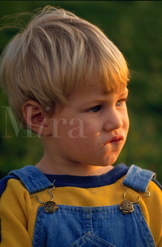 Young boy in overalls chewing on his lip looking thoughtful.