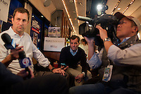 Traveling press secretary Felix Browne (center) records an interview while members of the media speak with Senator Scott Brown (R-MA) on his campaign bus between campaign stops in North Billerica and Wakefield, Massachusetts, USA, on Thurs., Nov. 2, 2012. Senator Scott Brown is seeking re-election to the Senate.  His opponent is Elizabeth Warren, a democrat.