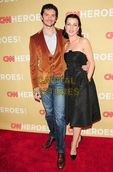 GABRIELE CORCOS & DEBI MAZAR .at The 3rd Annual CNN Heroes: An All-Star Tribute held at The Kodak Theatre in Hollywood, California, USA,  November 21st 2009                                                                   .full length strapless black dress hand in pocket brown jacket jeans married couple husband wife satin shoes  gold bracelet centre ruffle .CAP/RKE/DVS.©DVS/RockinExposures/Capital Pictures