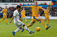 (L-R) Wayne Routledge of Swansea City gets a cross past Dan Burn of Wigan Athletic during the Sky Bet Championship match between Swansea City and Wigan Athletic at the Liberty Stadium, Swansea, Wales, UK. Saturday 29 December 2018
