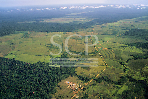 Amazon, Brazil. Aerial view of remote settlement on partly deforested land also showing a long straight road.