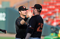 First baseman Christian Walker (23), left, of the Delmarva Shorebirds congratulates closing pitcher Matthew Price (25) after Price picked up the save in a game against the Greenville Drive on Monday, April 29, 2013, at Fluor Field at the West End in Greenville, South Carolina. Both players were on the National Champion University of South Carolina Gamecocks. Delmarva won, 6-5. (Tom Priddy/Four Seam Images)