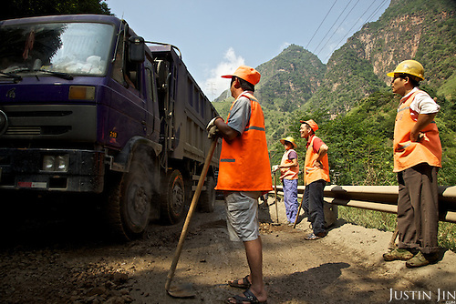 Workers repair a road in Sichuan province.
