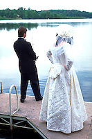 Groom fishing on dock as bride waits impatiently age 27. Roy Lake Nisswa  Minnesota USA