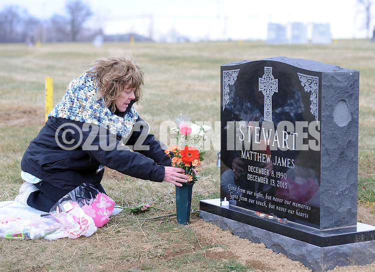 Rosemary Stewart places flowers at the gravesite of her son, Matthew Stewart Thursday, February 2, 2017 at All Saints Cemetery in Newtown, Pennsylvania. Stewart had purchased a family plot, and the cemetery people placed her son's gravesite too close to the street, leaving the family unable to place the tombstone they had chosen. After much back and forth the cemetery agreed to move the casket over to the next plot further away from the street, thus enabling the tombstone to be placed at the grave. (WILLIAM THOMAS CAIN / For The Philadelphia Inquirer)