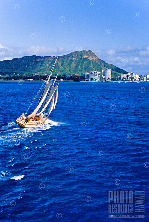 White sailboat making a sharp turn in deep blue water with Diamond head in the background