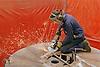 Man using circle grinder at engineering works,
