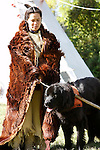 A Native American Lakota Sioux Indian woman in a buffalo robe with a dog travois